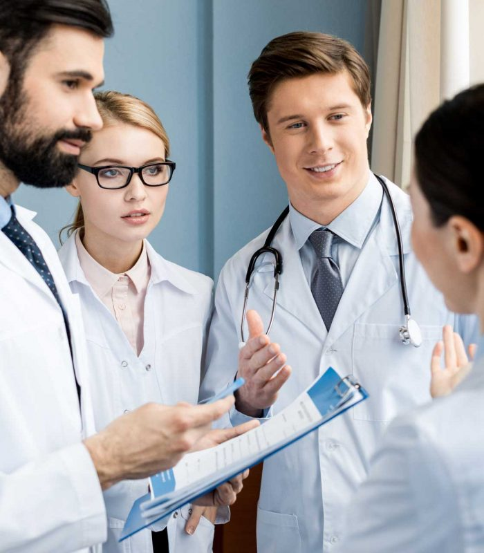 side-view-of-doctors-team-discussing-diagnosis-in-H9FJMNX.jpg